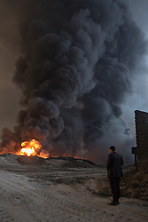 Licensed to London News Pictures. 20/10/2016. An Iraqi man observes plumes of thick smoke billowing from several oil wells on the edge of the neighbourhood where he lives in Qayyarah, Iraq. The wells, part of a large oilfield around the town, were set alight by retreating Islamic State militants in July 2016, but have yet to be extinguished. <br /> <br /> Since being retaken from the Islamic State the town of Qayyarah has become an important staging post for the Iraqi Army, and some US support elements, in the buildup to the Mosul offensive. Photo credit: Matt Cetti-Roberts/LNP