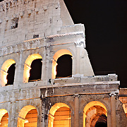 A telephoto shot of part of the ruins of the Coliseum of Rome, Italy, under lights at night.