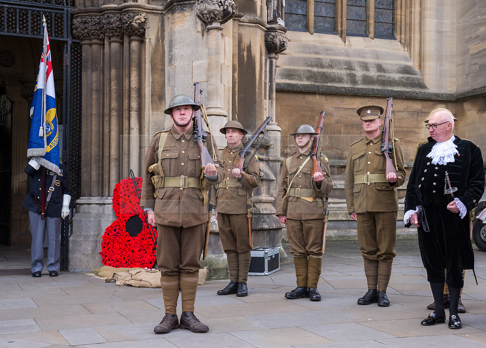 """© Licensed to London News Pictures. 27/10/2018. Bristol, UK. The Royal British Legion launch this year's Bristol Poppy Appeal, """"One thousand poppies, for one hundred years, for one million lives"""" at Bristol Cathedral. For the launch of the 2018 Bristol Poppy Appeal at 11am on 27 October, the Royal British Legion recreated a scene from the end of WW1 outside Bristol Cathedral on College Green, and Colonel Clive Fletcher-Wood read the war poem In Flanders Fields. They were joined by Civic Dignitaries Peaches Golding the Lord Lieutenant of Bristol, City of Bristol High Sheriff Mr Roger Opie (pictured), and Bristol's Lord Mayor Cleo Lake. A Bugler and the Bristol Military Wives Choir performed songs from their new album 'Remember'. Staff at MOD Filton filled 400 sandbags with eight tonnes of sand to build trenches and recreate 'Flanders Fields' and planted over 1000 waterproof poppies on College Green. Poppies and sandbags can be sponsored by individuals wanting to remember those who fought and died in conflict. There were re-enactors in WW1 uniform from Somerset Light Infantry (known as the West Country Tommys), as well as medics and nurses with equipment from the time. Bristol's own 'War Horse' (Buzz from Blagdon Horsedrawn Carriages) was on College Green behind the improvised barbed wire to represent the 350,000 horses that left Avonmouth for the frontline during WW1. There are also 10,000 knitted poppies on display both in and outside Bristol Cathedral following 'The Charfield Yarn Bombers' incitement to locals to get knitting to mark the occasion, with a display inside the Cathedral organised by Helen Date. Photo credit: Simon Chapman/LNP"""