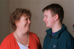 Middle aged woman and teenage son smiling at each other,