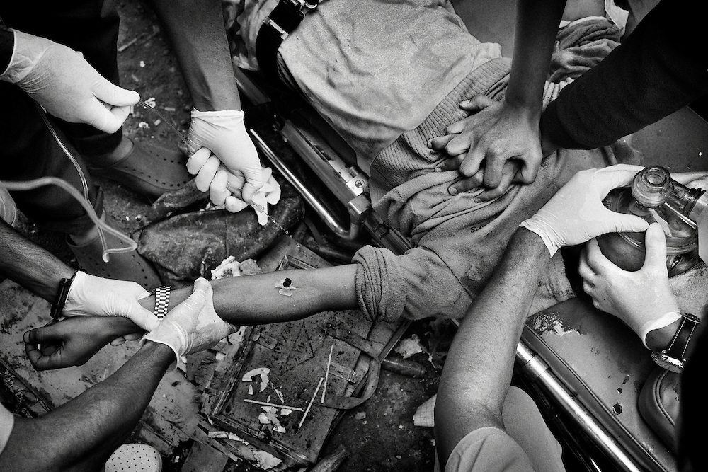 Medical staff members attempt unsuccessfully to keep an Anti-Qaddafi figther alive from a sniper shot on his neck during a street battle against loyalists to Col. Muammar el-Qaddafi for the city of Sirte, Libya, on October 13, 2011. Photo by Mauricio Lima for The New York Times