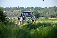 Female farm worker in tractor turning hay in summer