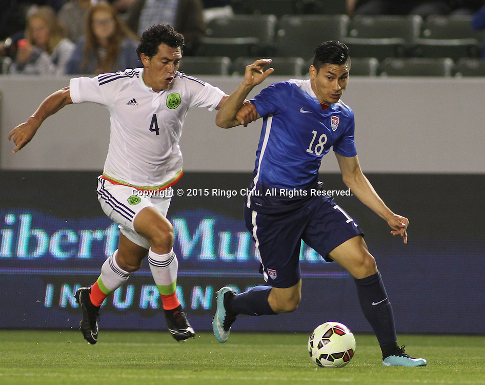 United States' Mario Rodriguez #18 actions against Mexico's Luis Guzm‡n #4 during a men's national team international friendly match, April 22, 2015, at StubHub Center in Carson, California. United States won 3-0. (Photo by Ringo Chiu/PHOTOFORMULA.com)