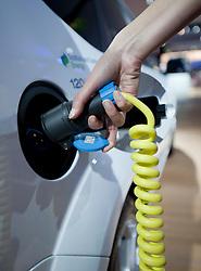 Recharging electric car using plug in charger at Frankfurt Motor Show 2009