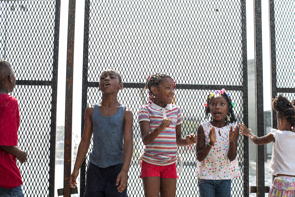 Children catch mist from a fountain outside the NASCAR Hall of Fame, next to a perimeter fence for the Democratic National Convention, on Monday, September 3, 2012 in Charlotte, NC.
