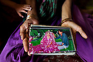 Sadma Khan, now 19, holds a wedding photo of she and her husband, Waseem Khan, now 26, as she sits in her mother's house in Tonk, Rajasthan, India, on 19th June 2012. She was married at 17 years old to Waseem Khan. The couple have an 18 month old baby and Sadma is now 3 months pregnant with her 2nd child and plans to use contraceptives after this pregnancy. She lives with her mother since Waseem works in another district and she can't take care of her children on her own. Photo by Suzanne Lee for Save The Children UK