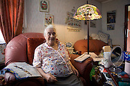 Pamela Clifton in the living room of her prefab at the Excalibur estate in Catford, South London. Pamela has been living in her prefab for 40 years and is fighting to save it as the Lewisham Council want to pull the prefabs down. Thousands of post-war prefabs are still being lived in and cherished by their tenants or owners all over the UK.