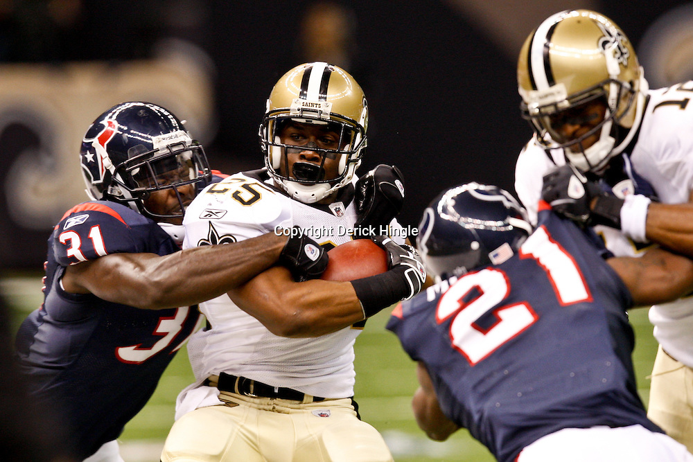 August 21, 2010; New Orleans, LA, USA; New Orleans Saints running back Reggie Bush (25) is grabbed by Houston Texans safety Bernard Pollard (31) during the first quarter of a preseason game at the Louisiana Superdome. Mandatory Credit: Derick E. Hingle