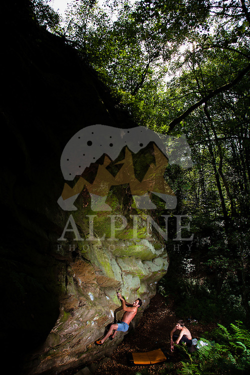 Antonio Caretta, an Italian climber, ascends an overhanging rock feature belonging to a former Nazi occult place deep in the forests surrounding Ibbenbüren, North Rhine-Westphalia, Germany on July 9 2011.