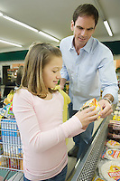 Father and daughter shop together in supermarket