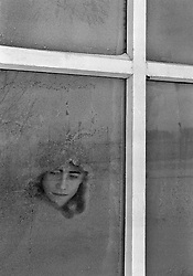Russian young prisoner looks through a frozen window standing inside the colony church for prisoner's children in Siberian town Leninsk-Kuznetsky, Russia, 25 January 2001.