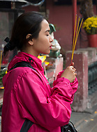 A woman holding incense sticks in the Jade Emperor Pagoda in Ho Chi MInh City, Vietnam, Southeast Asia