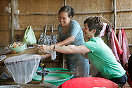 A tourist learns how to make rice paper at a popular tourist stop along the Mekong River in Vietnam  note: the American touris is model released<br /> <br />  photo by Dennis Brack