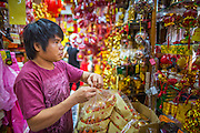 "22 JANUARY 2013 - BANGKOK, THAILAND:   A store employee puts Chinese New Year merchandise on display in a shop on Charoen Krung Road in Bangkok's Chinatown district. Chinese New Year is not an official public holiday in Thailand, but it is one the biggest celebrations in the Bangkok, which has a large Chinese population. Chinese New Year is February 10 this year. It will be the ""Year of the Snake.""    PHOTO BY JACK KURTZ"
