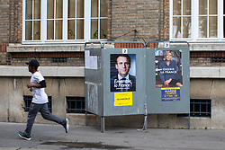 © Licensed to London News Pictures . 06/05/2017 . Paris , France . A man runs passed flyers for Macron and Le Pen in the Saint-Ouen district of Northern Paris . The electorate are voting in the final round of the French election today (7th May 2017) . Emmanuel Macron's En Marche and Marine Le Pen's Front National are competing for the Presidency . Photo credit: Joel Goodman/LNP
