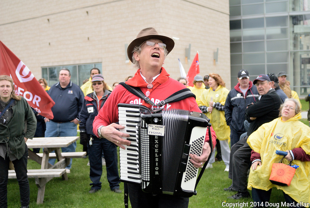Windsor, Canada, 2014,. Len Wallace, a musician and academic, plays accordion at the start of the annual May Day march. Wallace, a well known Windsor labour supporter, performs workers' themed songs and places them in a historical context.