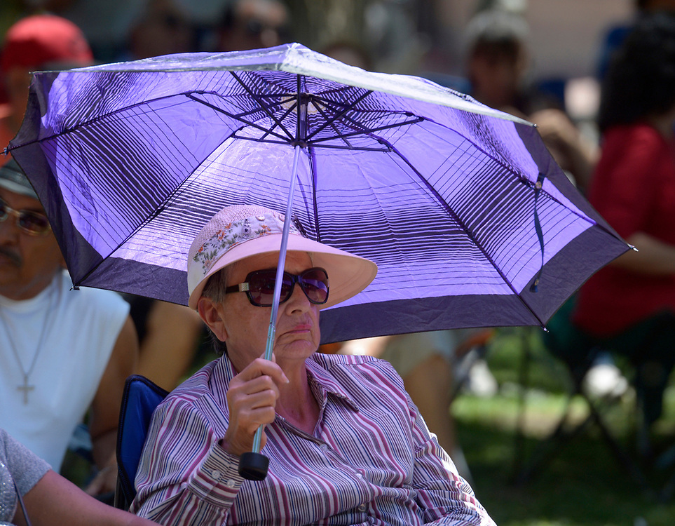 gbs060417e/ASEC -- Carmen Whatley of Albuquerque listens to the music of Mike Romero y La Raza in Old Town Plaza during the San Felipe de Neri Fiesta on Sunday, June 4, 2017. She said she attends the fiestas of all the Albuquerque churches. (Greg Sorber/Albuquerque Journal)