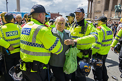 © Licensed to London News Pictures . 03/06/2017 . Liverpool , UK . An elderly anti fascist is pulled from the front of the crowd by police as anti-fascists attempt to block the EDL march . Hundreds of police manage a demonstration by the far-right street protest movement , the English Defence League ( EDL ) and an demonstration by opposing anti-fascists , including Unite Against Fascism ( UAF ) . Photo credit: Joel Goodman/LNP