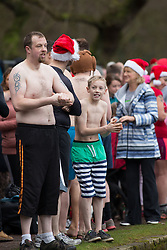 © Licensed to London News Pictures. 25/12/2016. Sutton Coldfield, West Midlands, UK. Due to the mild weather more swimmers than ever took part in the Sutton Coldfield Christmas morning swim. The morning plunge which takes place in Black Root pool has become an annual tradition. Picture shows swimmers getting ready for the swim. Photo credit: Dave Warren/LNP
