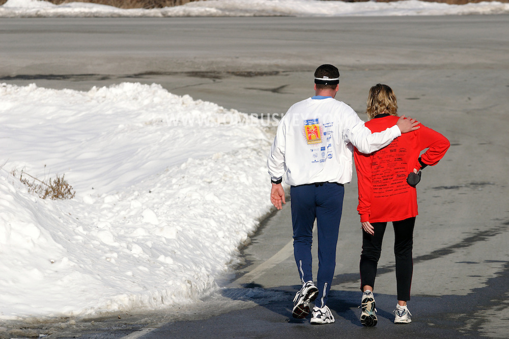 POCATELLO, N.Y. - A male and a female runner walk down the street after competing the Jingle Jog road race.Dec. 11, 2005.