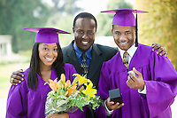 Father with two graduates outside portrait