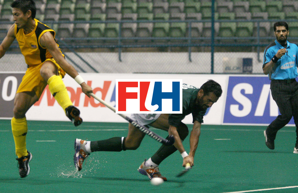 Kuala Lumpur:  Dilwar Hussain of Pakistan clears the ball from a Malaysian forward in the Samsung Hockey Men Champions Trophy on 03 Dec 2007.  Malayasia drew with Pakistan 2-2. .  Photo:GNN/Vino John