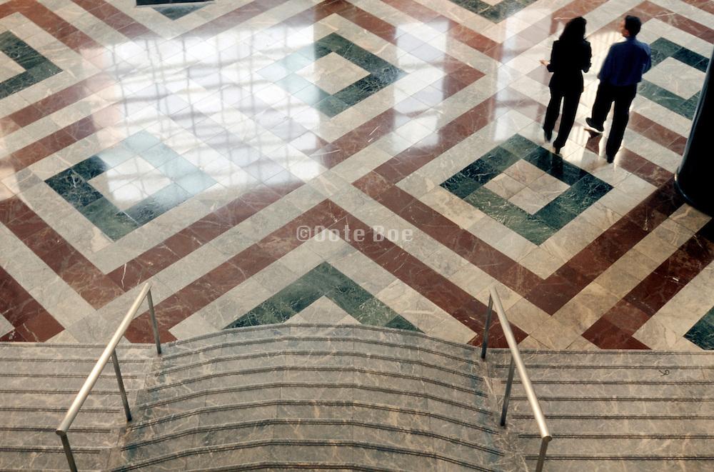 man and woman walking on shiny lobby floor