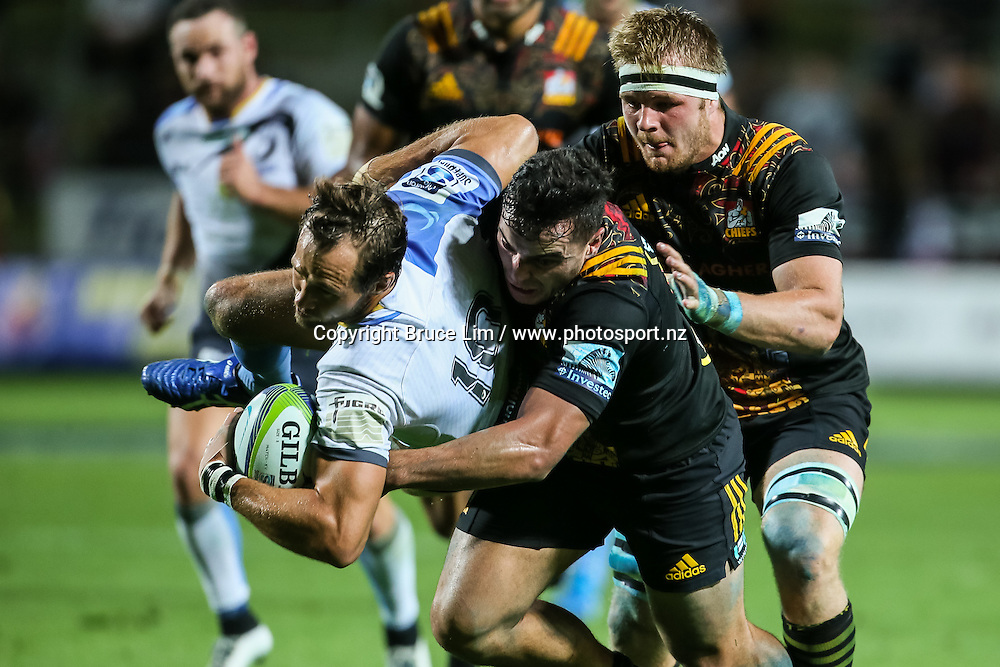 Western Force first five Peter Grant is smashed in a big tackled from Chiefs winger James Lowe during the Super Rugby match - Chiefs v Western Force played at FMG Stadium Waikato, Hamilton, New Zealand on Saturday 26 March 2016. <br /> <br /> Copyright Photo: Bruce Lim / www.photosport.nz