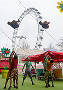 UNITED KINGDOM, London: 10 April 2018. Acrobats from Circus Abyssinia are launched in the air in front of the London Eye as they launch their headline run at the Underbelly Festival Southbank. The Ethiopian circus act Circus Abyssinia: Ethiopian Dream's will help celebrate 250 years of circus and 10 years of the Underbelly festival. Rick Findler / Story Picture Agency