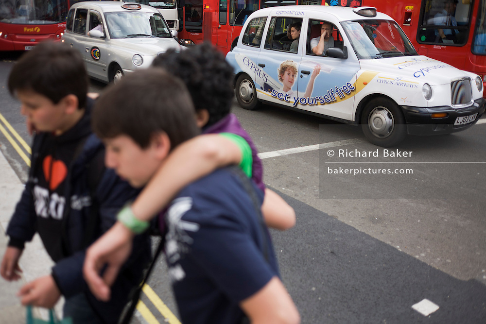Young boys cross the road in front of a holiday ad for Cyprus on a London taxi