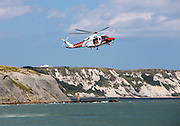 HM Coastguard rescue helicopter (G-C1JW) hovering in front of the white cliffs between Dover and Folkestone. Folkestone Harbour, Folkestone, Kent. UK. 6th August 2016. (photo by Andrew Aitchison / In pictures via Getty Images)