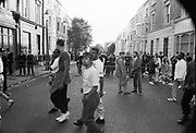 Crowd walking past police at barriers, Notting Hill Carnival, London, 1989