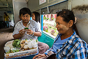15 JUNE 2013 - YANGON, MYANMAR:  A betel vendor, left, jokes with a customer on the Yangon Circular Train. Many Burmese chew betel, a mildly stimulating leaf which stains the teeth red. The Yangon Circular Railway is the local commuter rail network that serves the Yangon metropolitan area. Operated by Myanmar Railways, the 45.9-kilometre (28.5mi) 39-station loop system connects satellite towns and suburban areas to the city. The railway has about 200 coaches, runs 20 times and sells 100,000 to 150,000 tickets daily. The loop, which takes about three hours to complete, is a popular for tourists to see a cross section of life in Yangon. The trains from 3:45 am to 10:15 pm daily. The cost of a ticket for a distance of 15 miles is ten kyats (~nine US cents), and that for over 15 miles is twenty kyats (~18 US cents). Foreigners pay 1 USD (Kyat not accepted), regardless of the length of the journey.    PHOTO BY JACK KURTZ