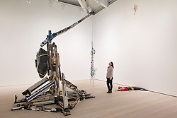 © Licensed to London News Pictures. 19/11/2013. London, UK. A Saatchi Gallery employee views 'Vandal Lust' (2011), an installation consisting of a trebuchet catapult, a body and an impact point by Romanian artist Andra Ursuta, at the press view for 'Body Language' a new exhibition at the gallery in London today (19/11/2013). Focussing on the human form, the exhibition features the work of 19 emerging international artists and opens to the public on the 20th of November 2013. Photo credit: Matt Cetti-Roberts/LNP