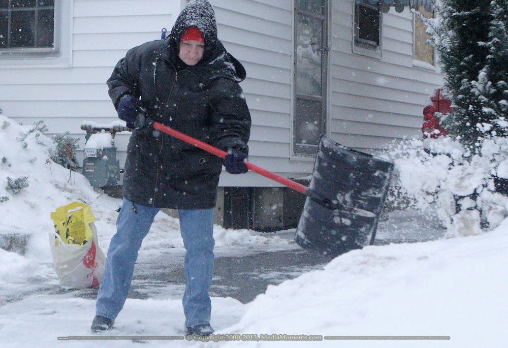 After husband Bill removed the first several inches of snow from their Belmont driveway in Dayton, Kathy Dyke gets down to the ground a second time, and will be putting salt out as well.