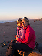 A mother and daughter enjoy sunset on the beach at Hokitika, New Zealand.