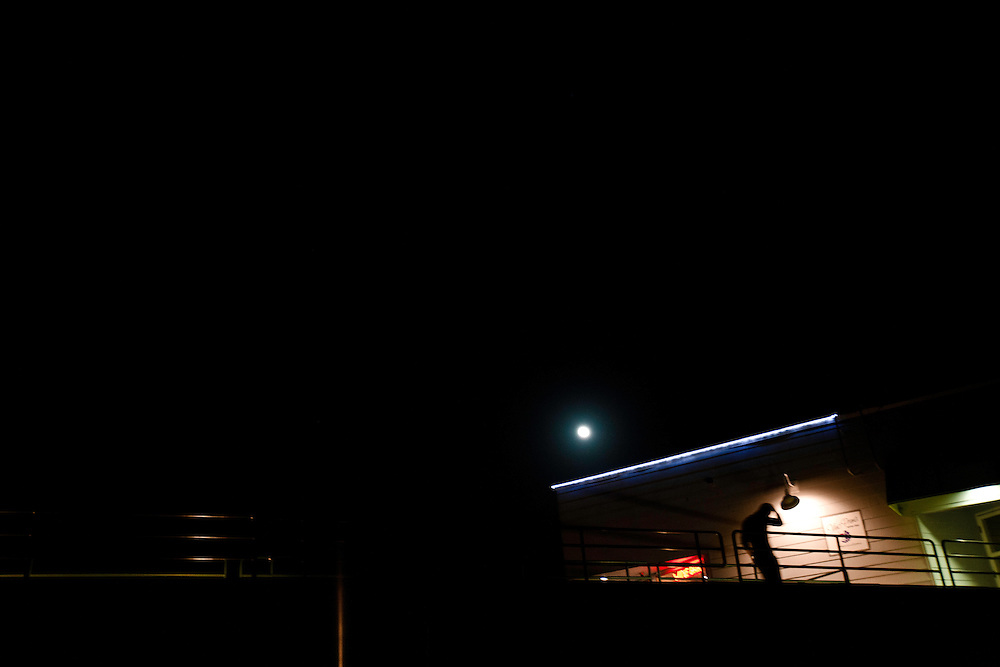 Man walks at night near Santa Cruz Boardwalk, in Santa Cruz, CA. Copyright 2014 Reid McNally.