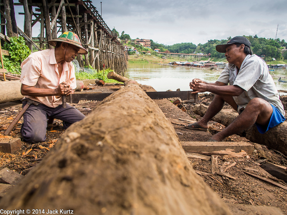 16 SEPTEMBER 2014 - SANGKHLA BURI, KANCHANABURI, THAILAND: Members of the Mon community saw a pylon for use on the Mon Bridge. The 2800 foot long (850 meters) Saphan Mon (Mon Bridge) spans the Song Kalia River. It is reportedly second longest wooden bridge in the world. The bridge was severely damaged during heavy rainfall in July 2013 when its 230 foot middle section  (70 meters) collapsed during flooding. Officially known as Uttamanusorn Bridge, the bridge has been used by people in Sangkhla Buri (also known as Sangkhlaburi) for 20 years. The bridge was was conceived by Luang Pho Uttama, the late abbot of of Wat Wang Wiwekaram, and was built by hand by Mon refugees from Myanmar (then Burma). The wooden bridge is one of the leading tourist attractions in Kanchanaburi province. The loss of the bridge has hurt the economy of the Mon community opposite Sangkhla Buri. The repair has taken far longer than expected. Thai Prime Minister General Prayuth Chan-ocha ordered an engineer unit of the Royal Thai Army to help the local Mon population repair the bridge. Local people said they hope the bridge is repaired by the end November, which is when the tourist season starts.    PHOTO BY JACK KURTZ