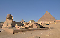 Giza complex in Egypt showing the Sphinx, 2 pyramids and some ruins with steps.