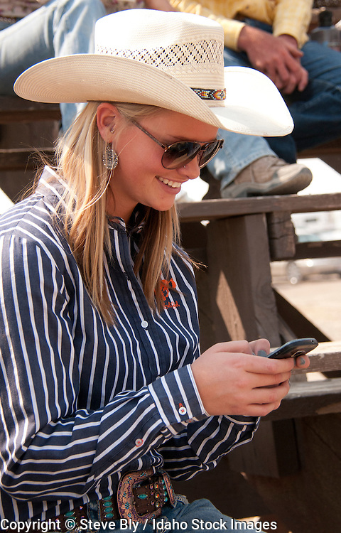 Cowgirl with cell phone enjoying the Rodeo, Bruneau, Idaho, USA