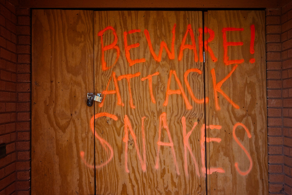 """""""Beware! Attack Snakes"""" spray painted on the temporary front door of a home in the Lakeview area that suffered major damage due to Hurricane Katrina flooding in New Orleans, Louisiana. Many of these homes' interiors remain untouched; floors are covered in flood debris and rubble while the walls and surfaces are still scab-covered layers of mold."""