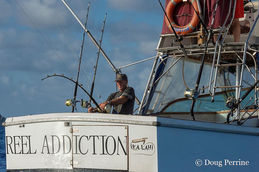 Captain Steve Campbell, fighting a fish aboard Reel Addiction, off Hunga Island, Vava'u, Kingdom of Tonga, South Pacific