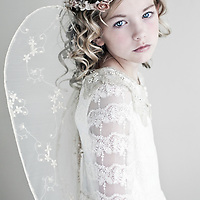 Female youth with blonde hair and blue eyes wearing lace dress and angels wings with frown of small flowers