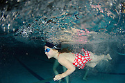 Girl of five with goggles swims underwater