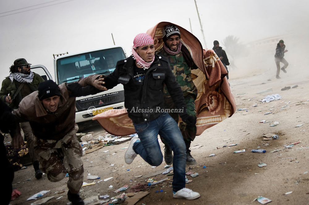 """LIBYA, BREGA : Anti Libyan government fighters rush for cover as heavy shelling by forces loyal to Libyan strongman Moamer Kadhafi fall close to their position in the eastern town of Brega on March 13, 2011. Libyan state television said the town had been """"purged"""" of insurgents. ALESSIO ROMENZI"""
