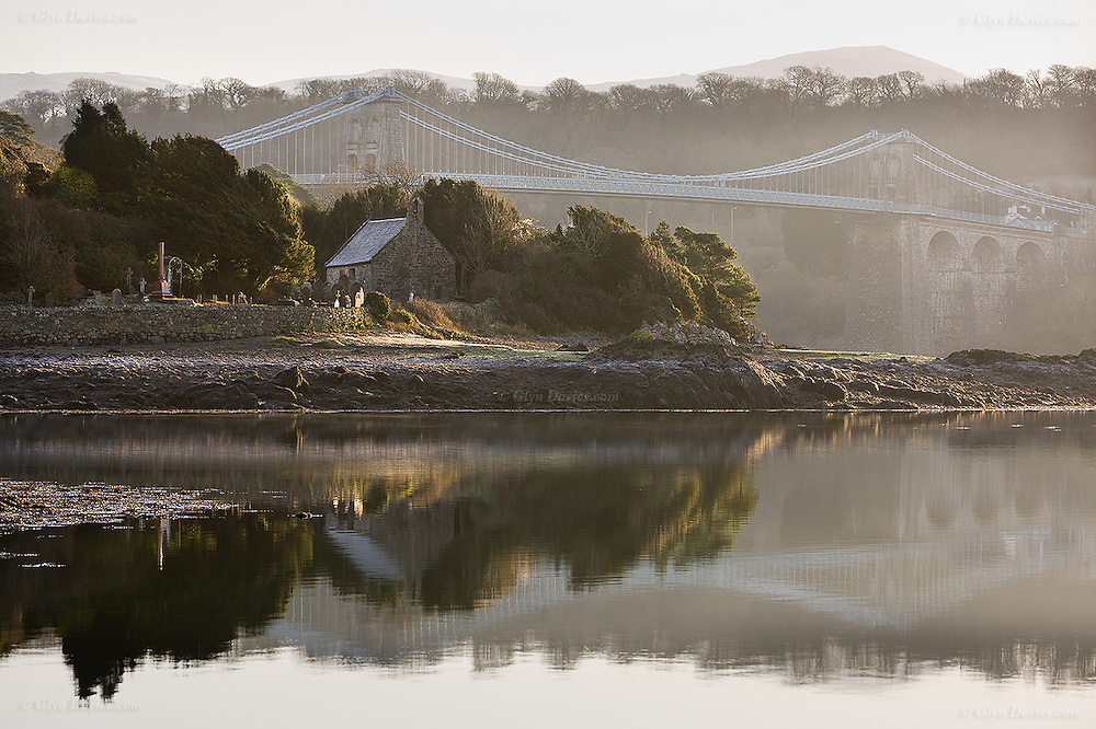 An eary morning mist over the tidal Menai Strait, shrouding the idyllic church and graveyard of St Tysilio Island, Anglesey. Menai Suspension Bridge (Welsh: Pont Grog y Borth) is a stone built Victorian suspension bridge between the island of Anglesey and Bangor and mainland of Wales. The 100ft high bridge was designed by Thomas Telford and completed in 1826. It stands proud of the small church island