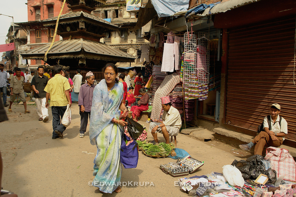 Hindu woman walks in a busy street with temple in the background in Kathmandu's old town.