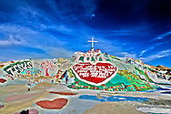 "Salvation Mountain is located in the lower desert of Southern California in Imperial County just east of the Salton Sea. Salvation Mountain is Leonard Knight's tribute to God and his gift to the world with its simple yet powerful message: ""God Is Love."" Leonard's passion has created this brilliant ""outsider art "" masterpiece resplendent with not only biblical and religious scripture such as the Lord's Prayer, John 3:16, and the Sinner's Prayer, but also including flowers, trees, waterfalls, suns, bluebirds, and many other fascinating and colorful objects. Its 50 foot height and 150 foot breadth is made totally of local adobe clay and donated paint and is truly unique in the United States and probably the world. From its Sea of Galilee at the bottom, to the big red heart in the middle, to the cross at the very top, the reoccurring theme of ""Love"" is everywhere at Salvation Mountain. Niland, California"