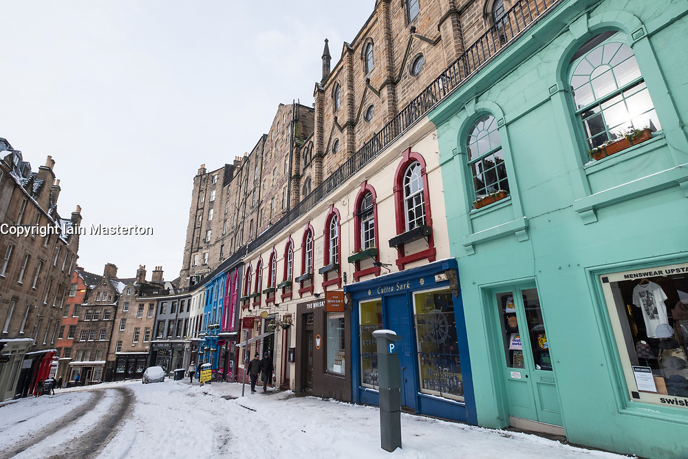 View of colourful shop fronts on historic Victoria Street in Edinburgh Old Town after heavy snow, Scotland, United Kingdom