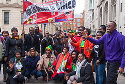 Lodon, February 21st 2015. Dozens of exiled Zimbabweans gather outside their embassy in London proclaiming Mugabe's last birthday in office. Singing and dancing as they have done every Saturday since 2002, the group spoke with passersby and added yet more names to their petition. PICTURED: Zimbabwe Vigil protesters pose with a banner proclaiming this birthday - his 91st - is Mugabe's last in office.